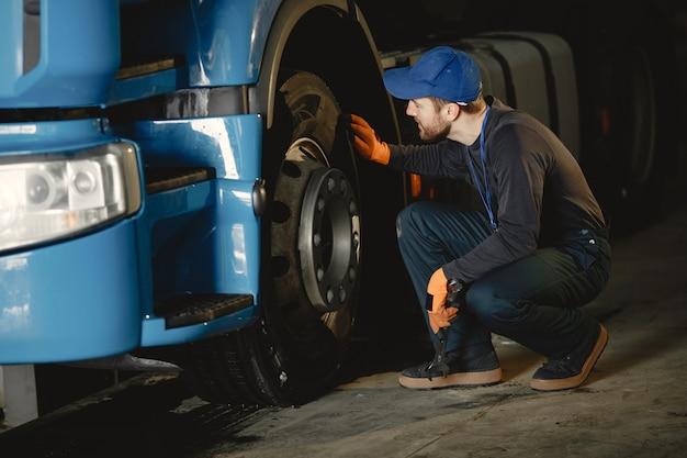 若い労働者が車輪をチェックします。トラックの故障。サービス作業。