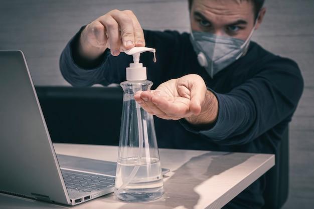 Молодой рабочий в медицинской маске работает рано утром из дома. пандемия коронавируса covid 19. человек обрабатывает руки дезинфицирующим средством для дезинфекции и уничтожения опасных вредных микробов.