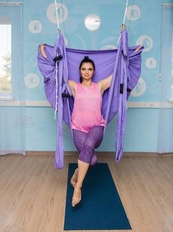 Молодая женщина-йога сидит в фиолетовом гамаке в студии