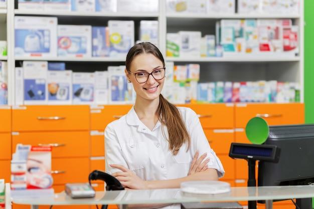 안경을 쓴 젊고 유쾌한 검은 머리 소녀, 의료용 옷을 입고 새 약국의 계산대에서 방문객을 맞이합니다. .