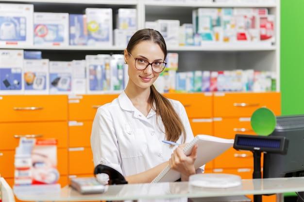 안경을 쓴 젊고 유쾌한 검은 머리 소녀는 의료용 옷을 입고 새 약국의 계산대에 있는 공책에 메모를 씁니다. .