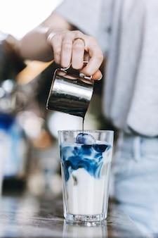 Юная симпатичная стройная блондинка в повседневной одежде наливает кофе в стакан молока в уютной кофейне. .