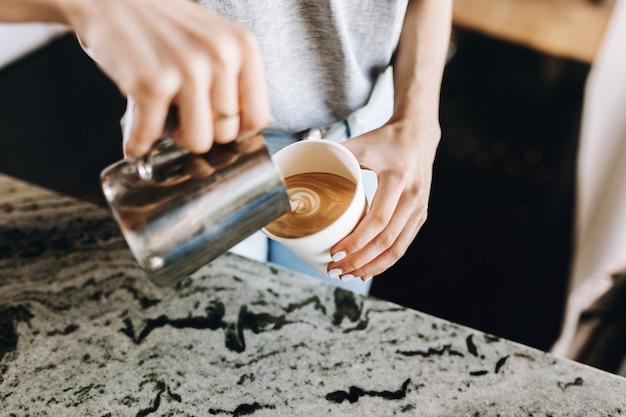 Юная стройная добрая блондинка, одетая в повседневную одежду, умело подливает молоко в кофе в современной кофейне. .