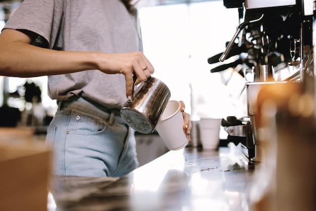 На фотографии изображена юная худощавая блондинка в повседневной одежде, добавляющая молоко в кофе в уютной кофейне. .