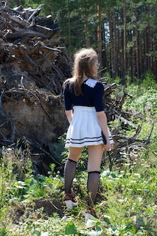 Девушка-зомби с топором в руках в мрачном лесу. костюм на хэллоуин
