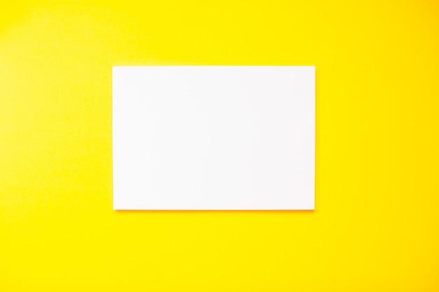 А4 пустой белый лист на ярко-желтом фоне.