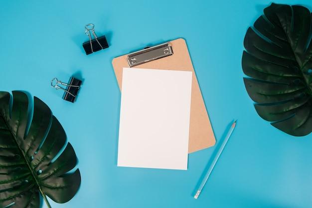 Плоский лежал макет бумаги a4 с буфером обмена, пальмовых листьев и карандаш на синем фоне.