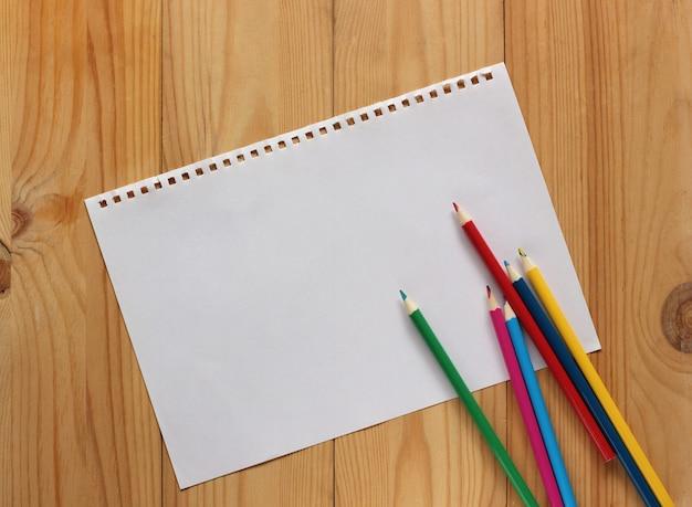 木製の床と色鉛筆、上面に白いa4紙のシート。