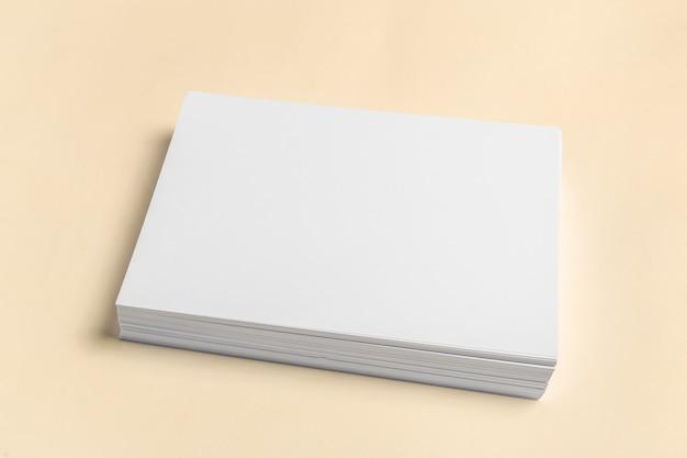 木製のテーブルの上の白い名刺。空白の肖像画a4。