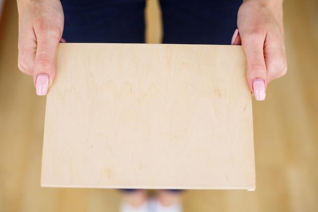 白い背景の上のaツリーボードを保持しているオフィスの女性手。コピースペース。テキストのための場所
