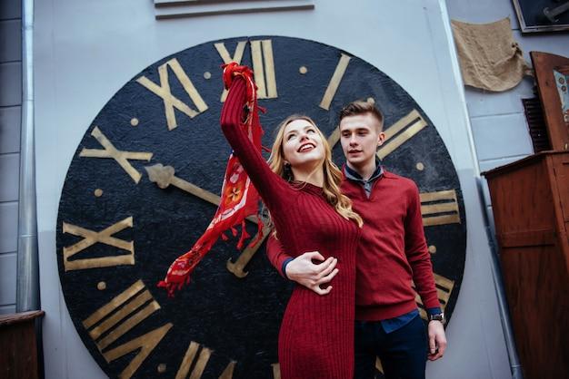 時計の近くに立って美しいスタイリッシュなカップルの肖像画。 a