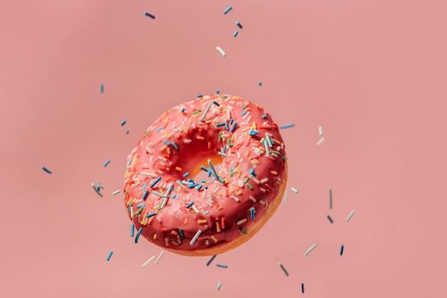 Большой вкусный пончик с розовой глазурью висит в воздухе на розовом фоне. a кондитерские украшения опрыскивают летающий пончик сверху. пончик падает