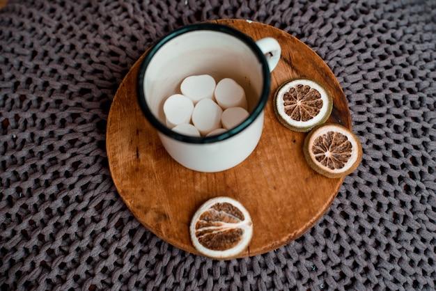 マシュマロaが付いている軽い木製のテーブルメタルマグカップに、テキストまたはイメージのための空のスペースがあります