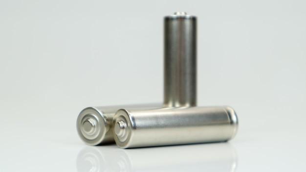 Щелочные аккумуляторные батареи aa на белом глянцевом фоне с отражением. закройте три пустые батареи с копией пространства.