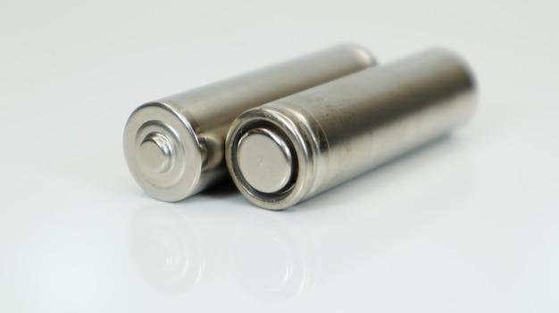 Щелочные аккумуляторные батареи aa на белом глянцевом фоне с отражением. закройте две пустые батареи с копией пространства.