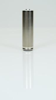 Щелочная аккумуляторная батарея aa на белом глянцевом фоне с отражением. закройте одну пустую батарею с местом для копирования. вертикальная фотография.