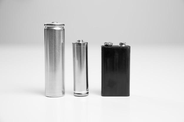 Aa и литий-ионный аккумулятор 8650 серебристый, батарея 9v черного цвета на белом фоне. одноразовые батарейки и аккумуляторы.
