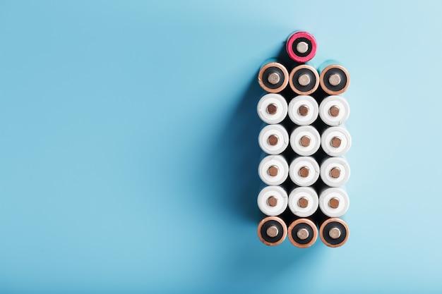 Пальчиковые батарейки аа в виде большой батарейки на синем фоне. концепция энергоснабжения, вид сверху на свободное пространство.