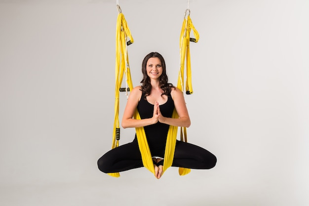 Aa young female sportswoman is engaged aeroyoga in a yellow hammock on a white isolated wall. namaste pose