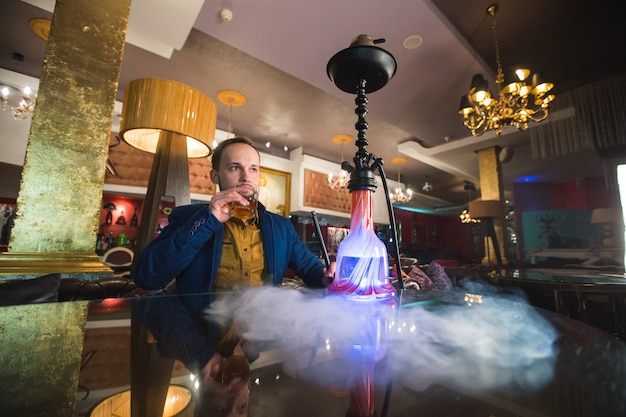 喫煙ギセル。男は煙を吹いています。 ââ