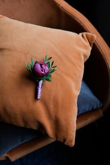 新郎のブートニアは、ホテルの部屋にあるaaオレンジ色の枕の上にあります。結婚式の日や朝。
