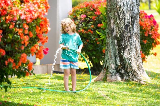 여름 저녁에 집 뒤뜰에 있는 정원에서 호스 스프레이로 식물에 물을 주는 사랑스러운 소년.