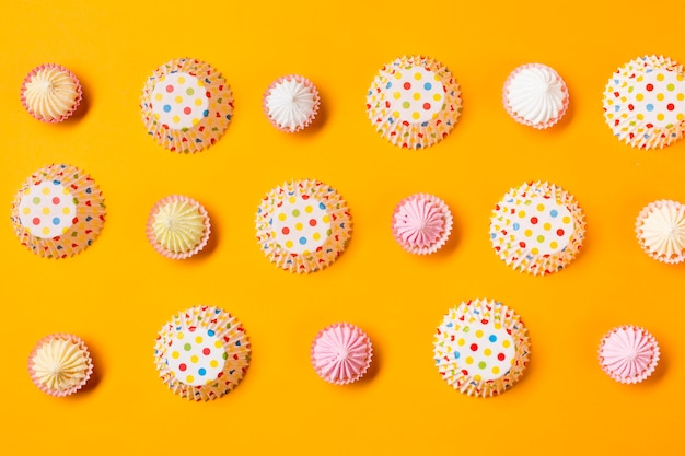 Aalaw with polka dots paper cake forms in a row on yellow background