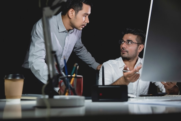 Aasian businessman coworkers discussing work at night