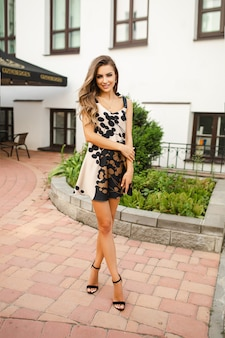 Una giovane donna caucasica attraente in abito corto e scarpe con una borsa in posa per la telecamera vicino al bellissimo edificio