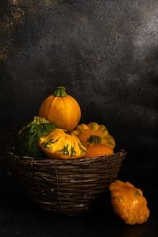 A秋の野菜、黄色いカボチャ、さまざまな種類のカボチャが暗い背景の籐のバスケットに入っています