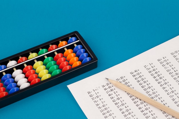 Abacus for mental arithmetic, on a blue background, with examples to solve.