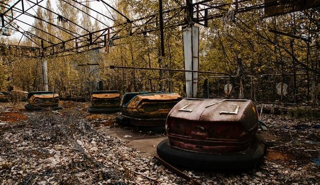 체르노빌 제외 구역에서 프리 피 야티 도시에서 녹슨 자동차와 함께 버려진 된 놀이 공원.