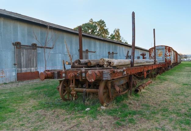いくつかの積み込まれた木の棒を備えた放棄されたさびた客車