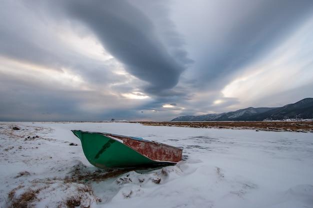 Заброшенная лодка зимой в снегу возле замерзшей реки и очень красивое небо с облаками