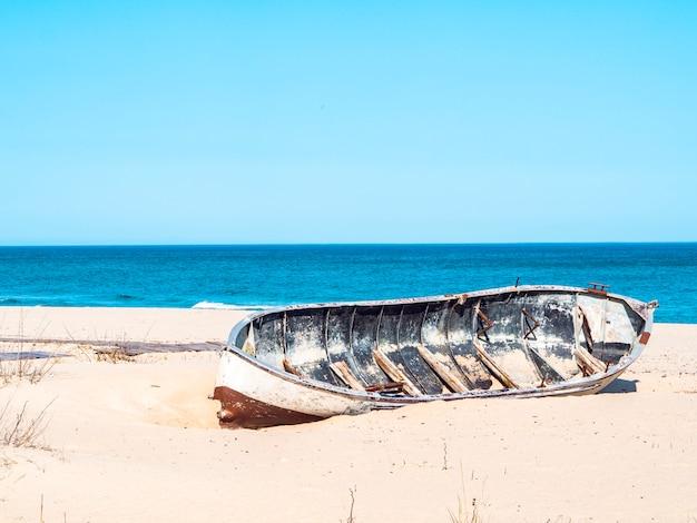 Брошенная лодка на песке. старая винтажная деревянная рыбацкая лодка на красивом белом тропическом пляже океана. чистое небо