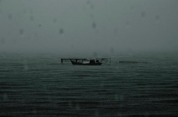 Abandoned boat rainy dark sea