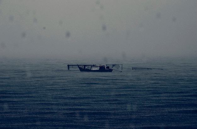 Abandoned boat rainy dark sea