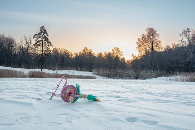Брошенный сломанный детский велосипед в снегу. конец концепции праздников.
