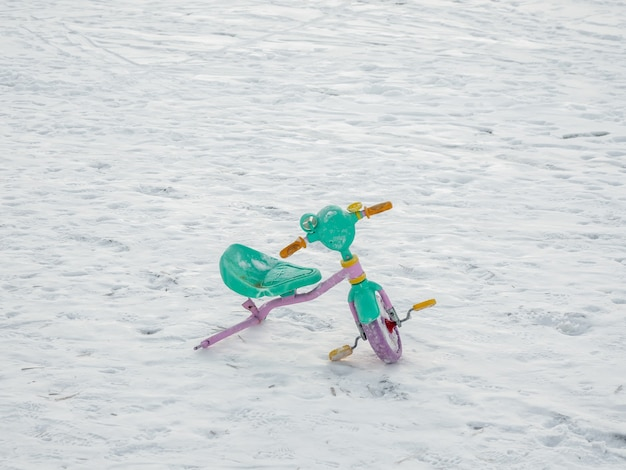 Abandoned broken children's bike in the snow. the end of the holidays concept.