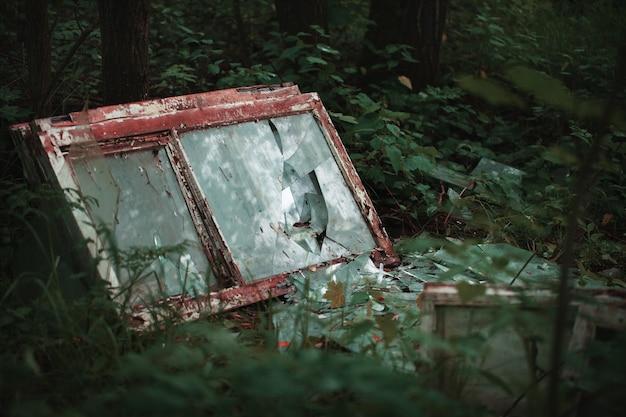 Заброшенные разбитые окна в лесу. загрязнение окружающей среды
