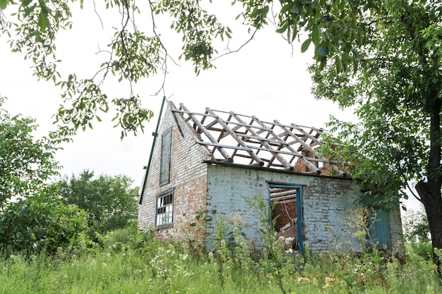 Abandoned building without a roof in an overgrown field