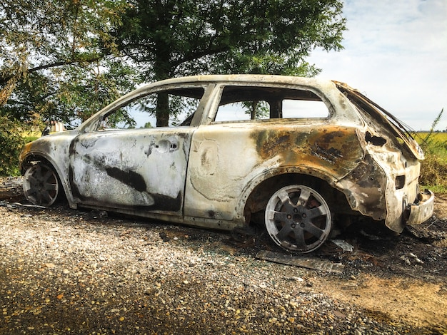Abandoned burnt car at isolated field