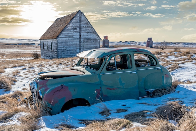 Abandoned car and church on a snowy hillside overlooking twin grain elevators in neidpath