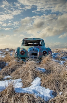 Abandoned car in the tall grass on a snowy hillside in neidpath