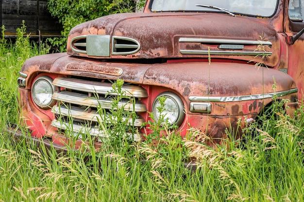캐나다 대초원의 키 큰 풀밭에 버려진 고전적인 빨간 픽업 트럭