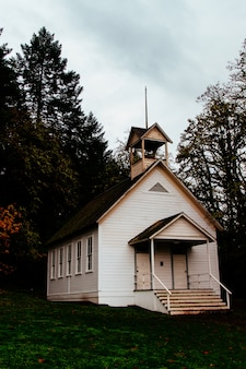 Abandoned closed wooden church in a forest in the countryside