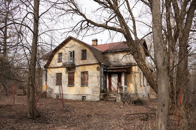 Abandoned country house among naked trees and dry fallen leaves.