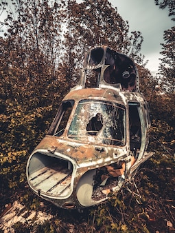 Abandoned destroyed cabin of old ussr helicopter with broken glass in the wild nature closeup