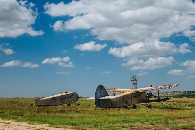 Abandoned, destroyed, rusty old planes stand on the grass under a blue sky with white clouds.