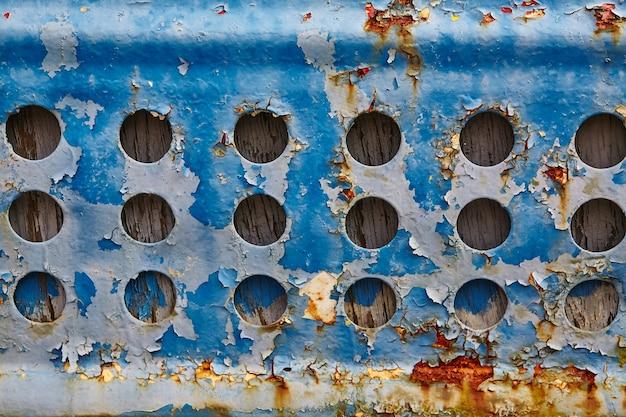 Заброшенная решетка с ржавчиной и отслаивающейся синей краской вокруг отверстий
